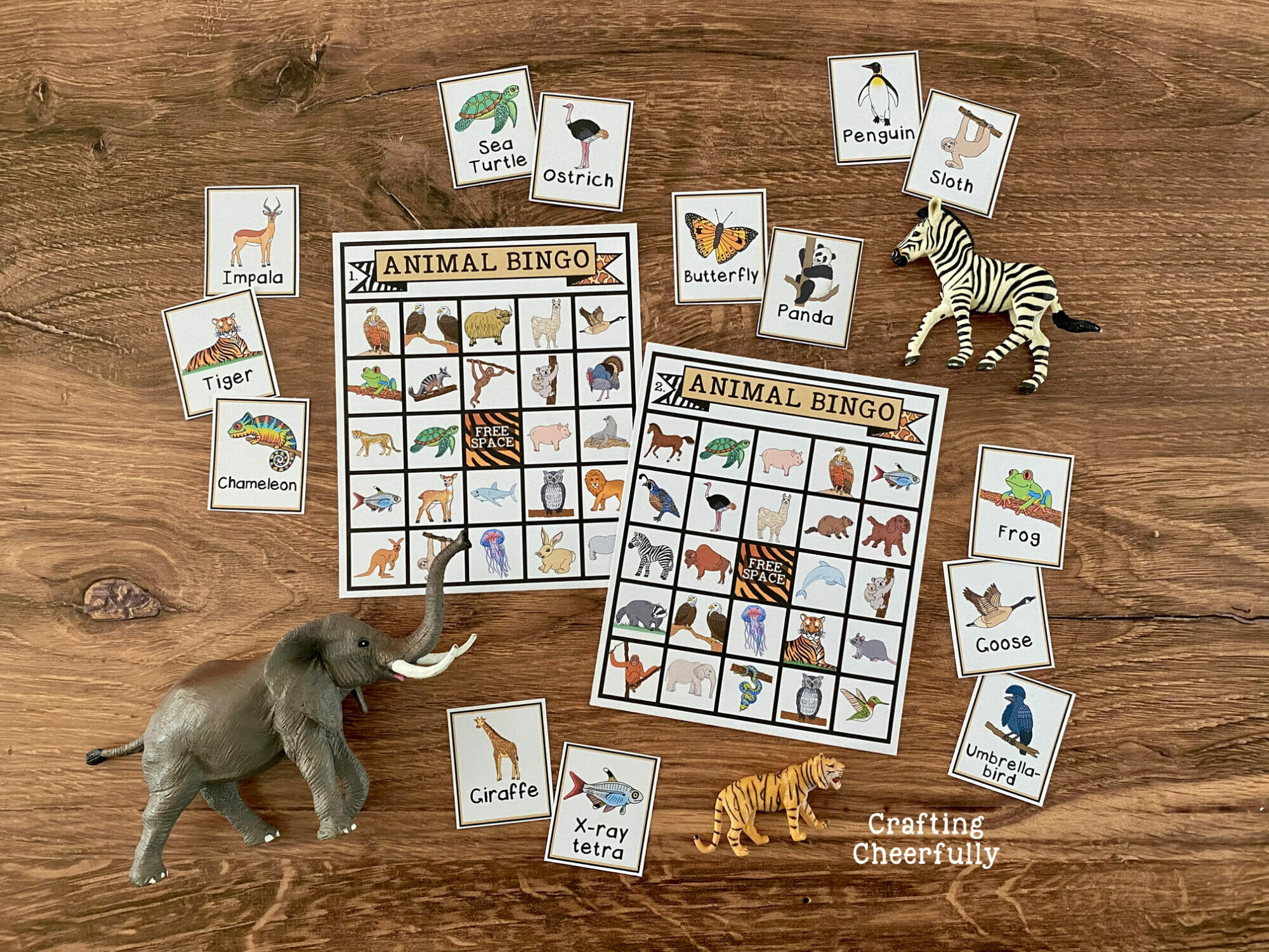 Animal BINGO boards on a wooden surface with calling cards and toy animals laying around them.