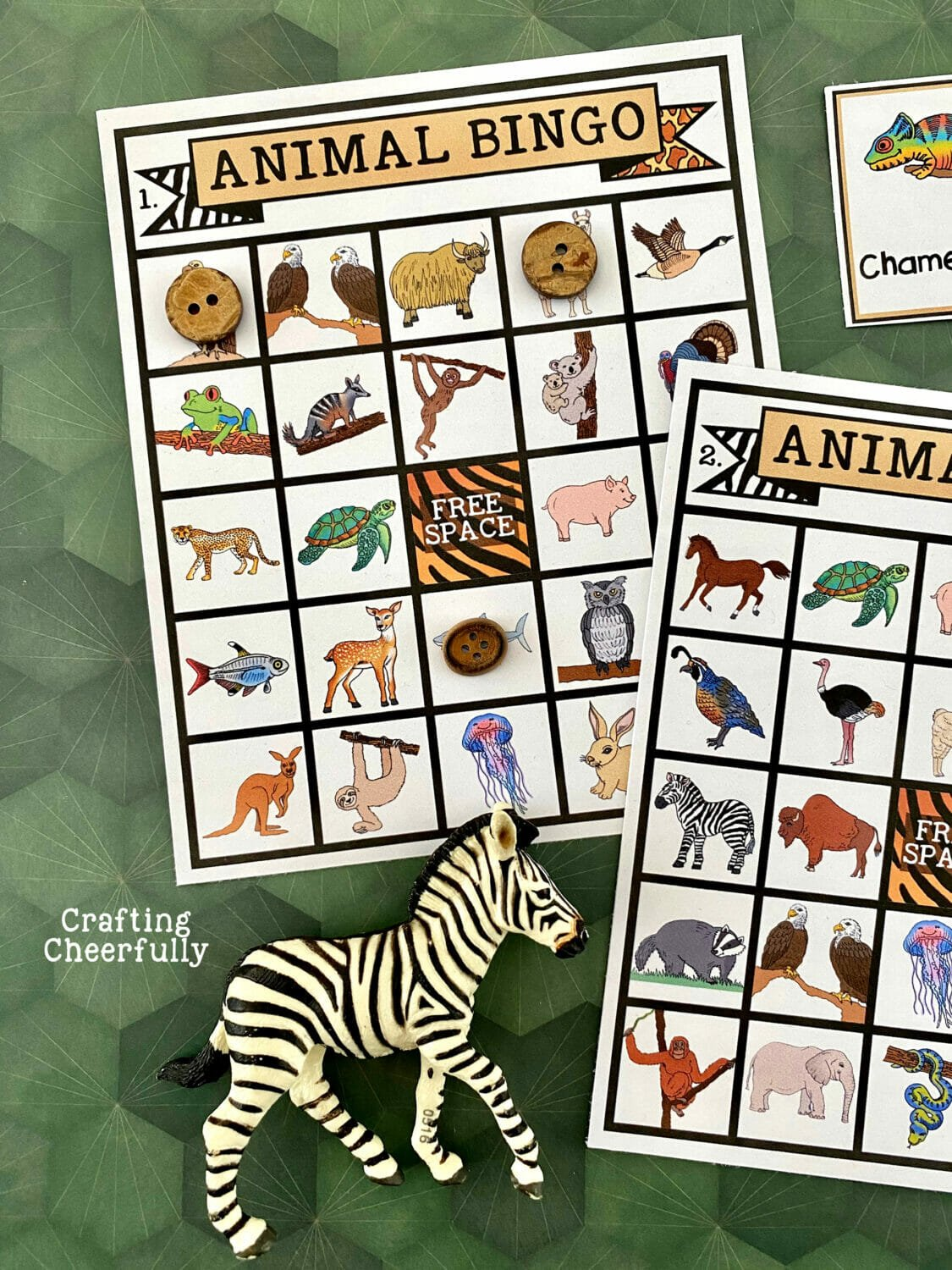 Animal BINGO boards on a green surface with calling cards and a zebra around them.