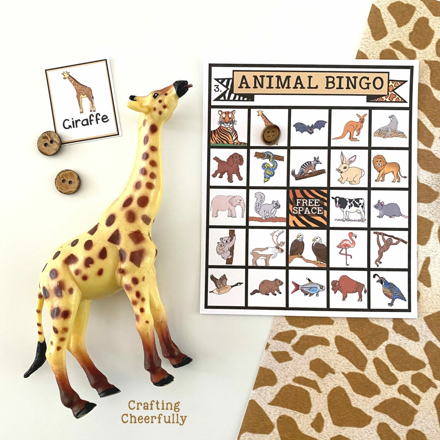 An animal BINGO board on a white and giraffe print surface with calling cards and toy giraffe laying around it