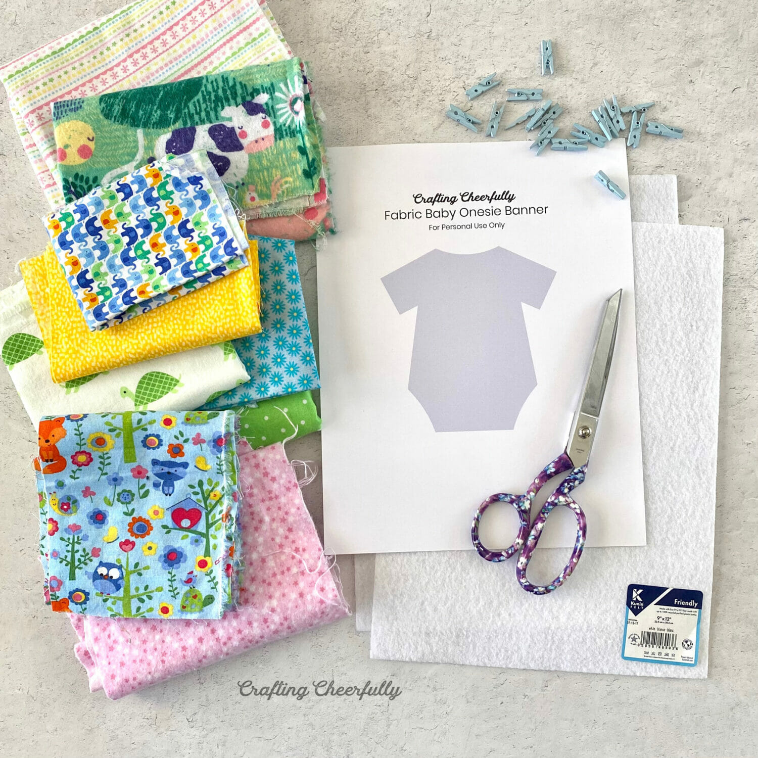 Supplies gathered together for making banner including fabric, scissors, felt, template and clothespins.