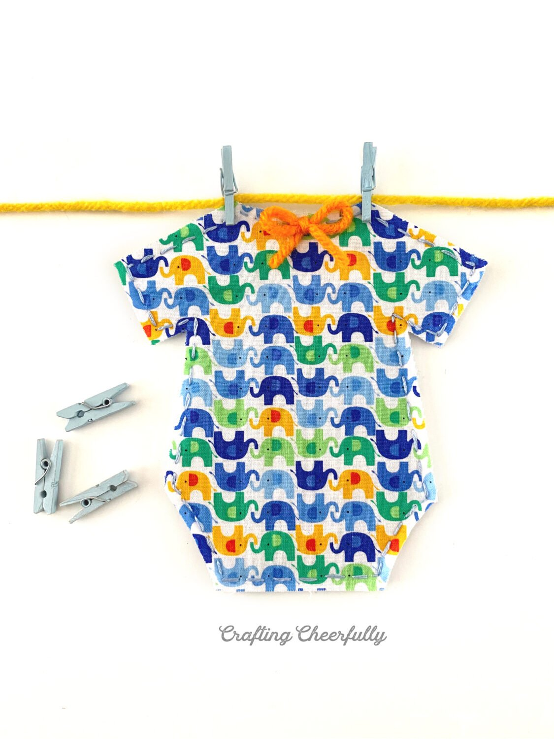 A cute fabric onesie with elephants on it hangs on a piece of yarn with mini clothespins.