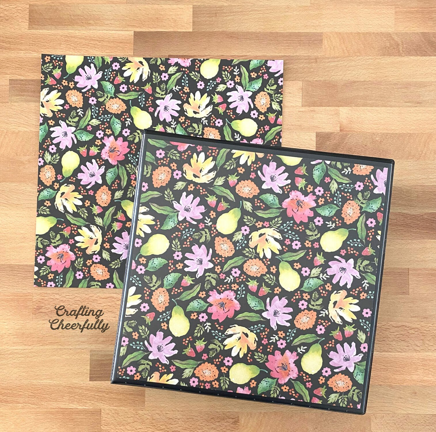 Black binder covered with floral paper on a kitchen counter.