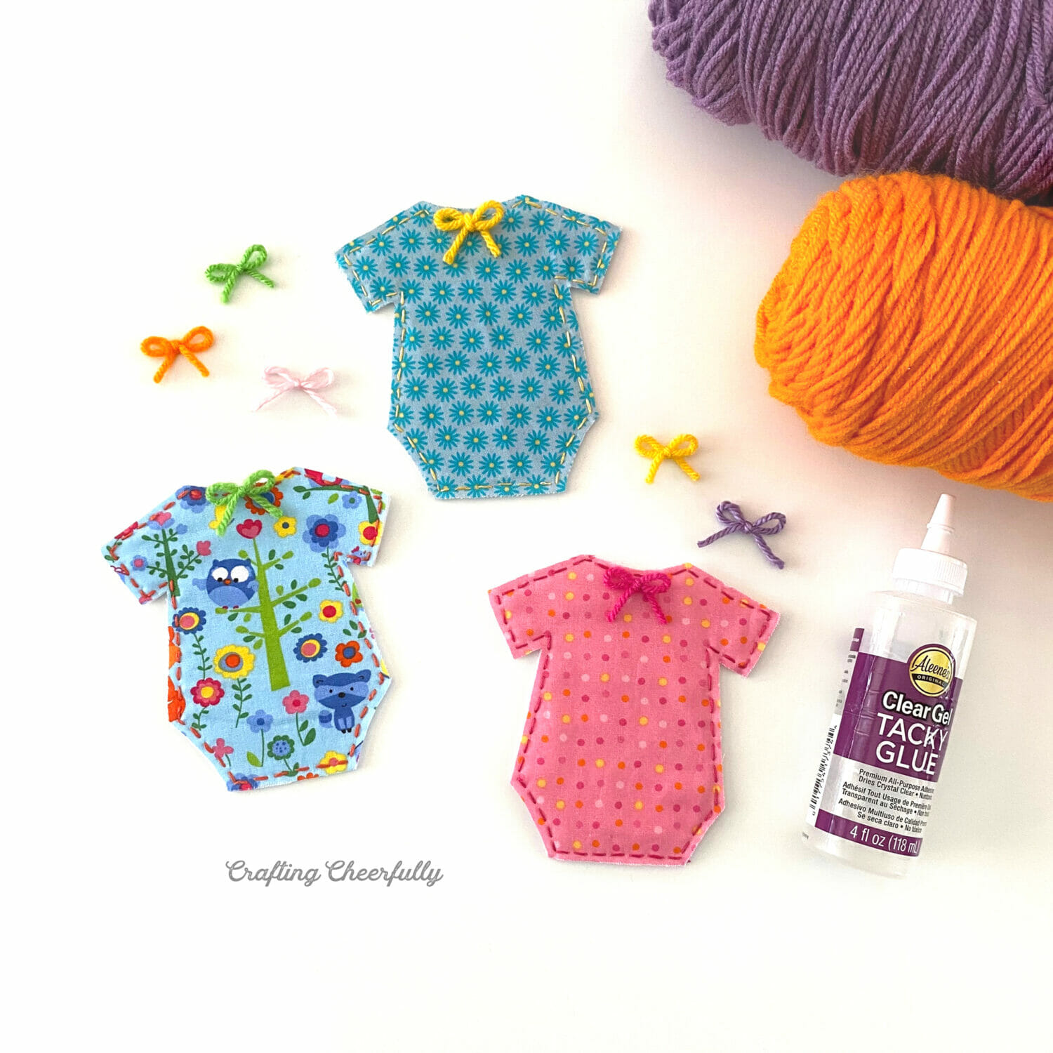 Cute fabric onesies for the banner lay next to yarn, tiny yarn bows and glue.