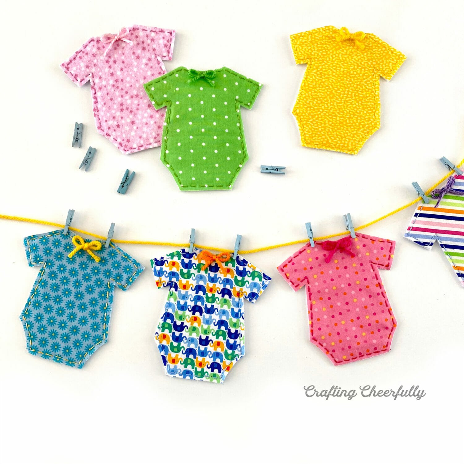 Tiny fabric onesies hang on yarn with mini clothespins to form a baby shower banner.
