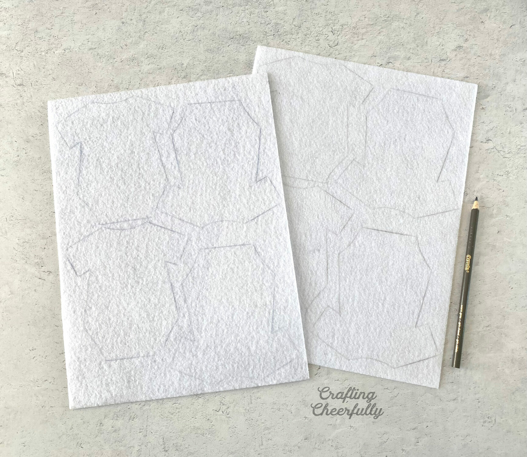 Sheets of white felt with onesies traced onto them.