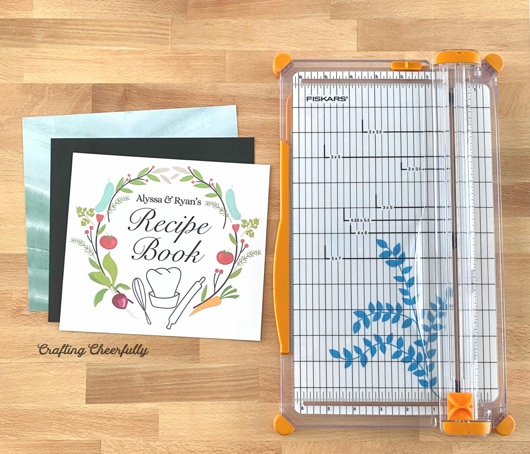 Recipe Binder Label and sheets of scrapbook paper next to a paper trimmer.