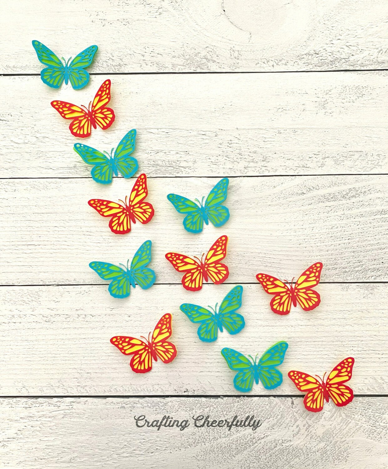 Red and yellow butterflies along with green and blue butterflies are arranged on a wooden surface.