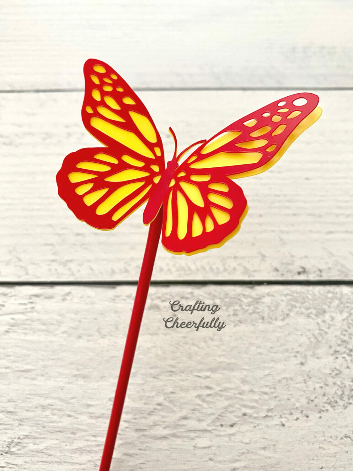 Close up picture of a red and yellow butterfly plant stake.