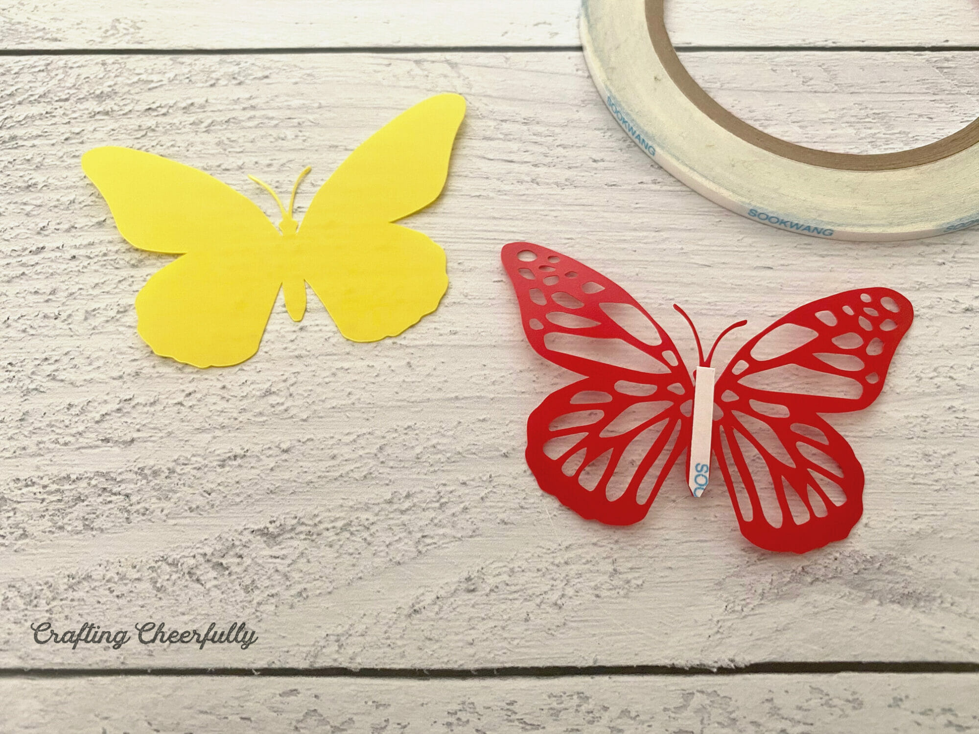 A yellow butterfly and a red butterfly with a cut out design lay next to each other, double-sided tape is on the back of the red one.