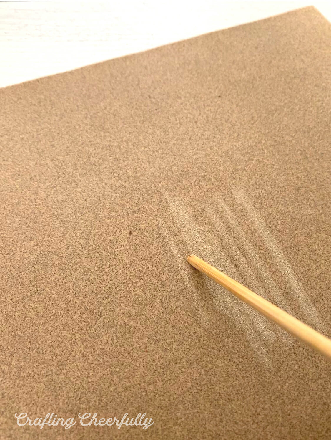 A dowel is rubbed against sand paper.