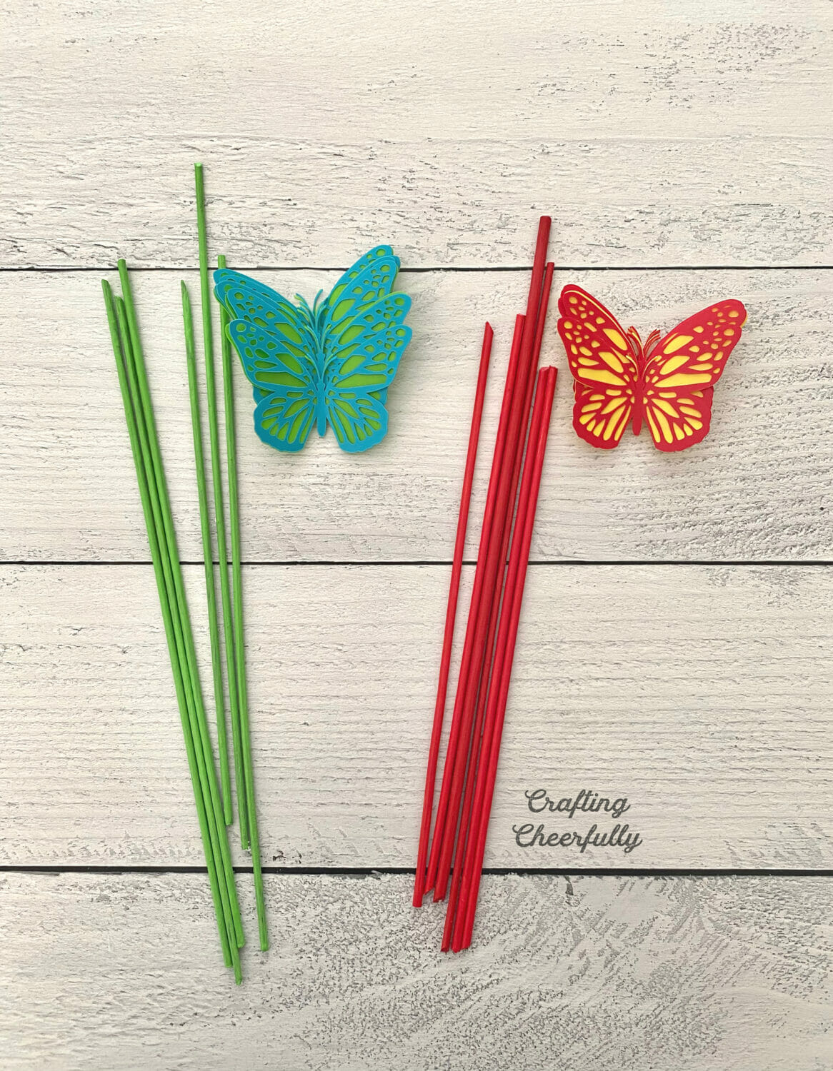 Painted wooden dowels and butterflies lay on a wooden surface.