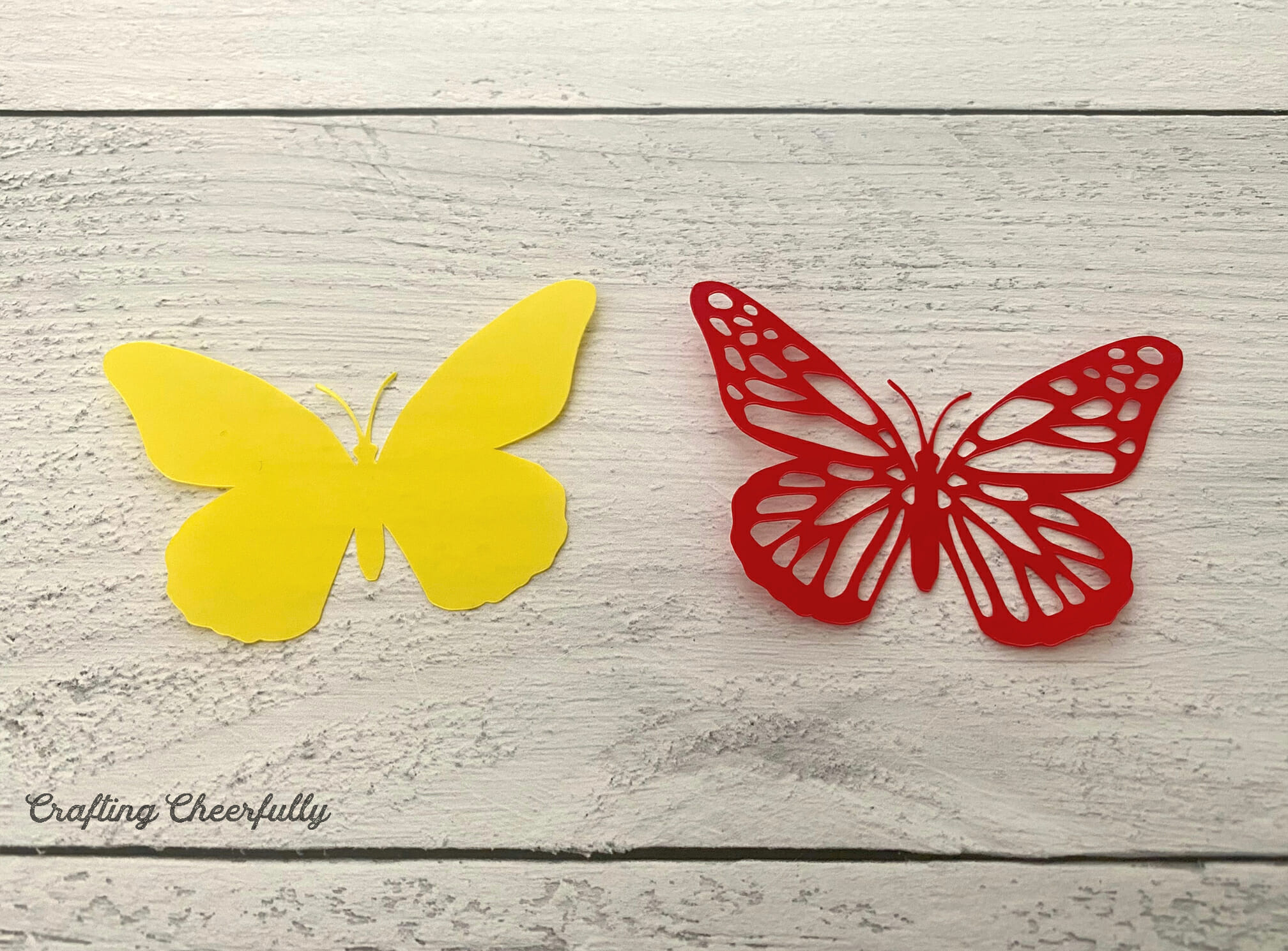 A yellow butterfly and a red butterfly with a cut out design lay next to each other.