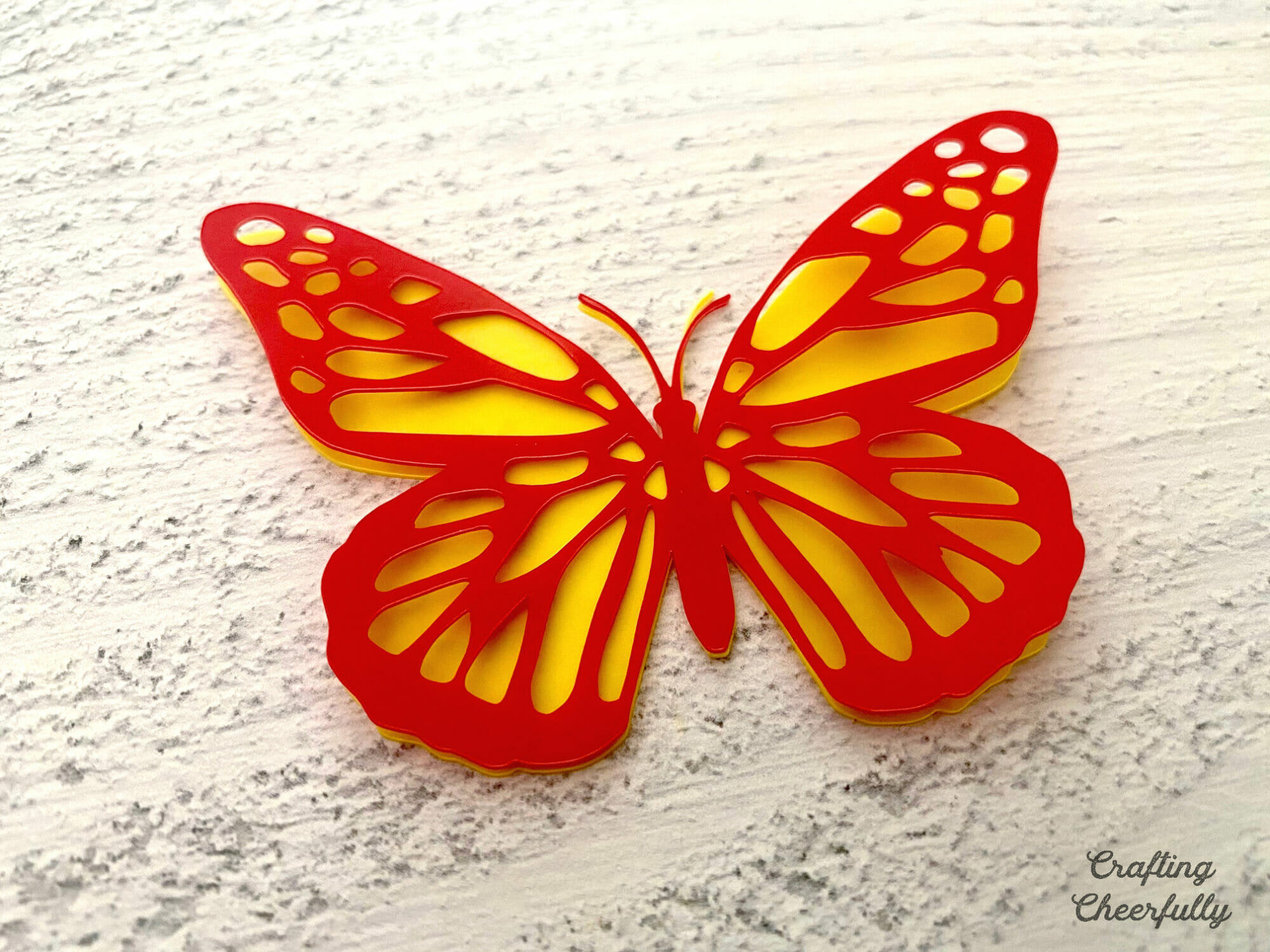 A red and yellow butterfly made from craft plastic.