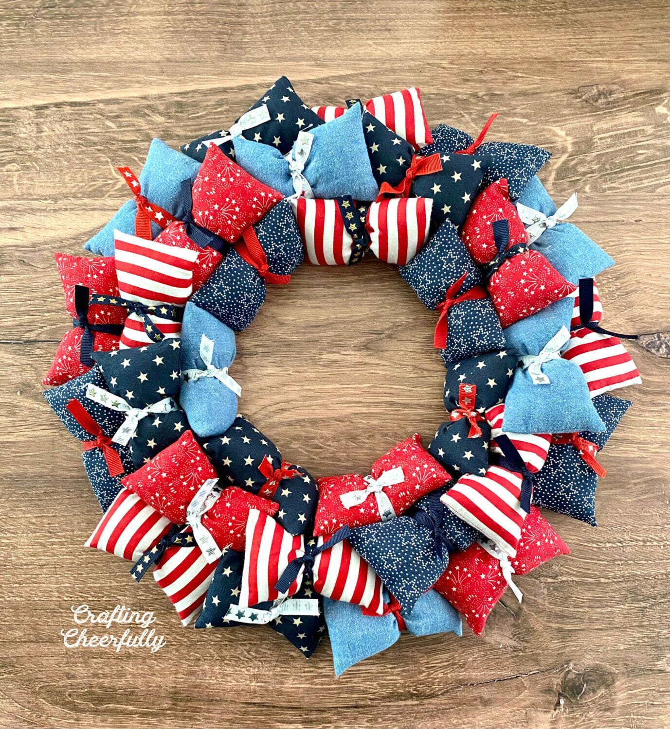 Pillow wreath made from red, white and blue fabric on a wooden background.