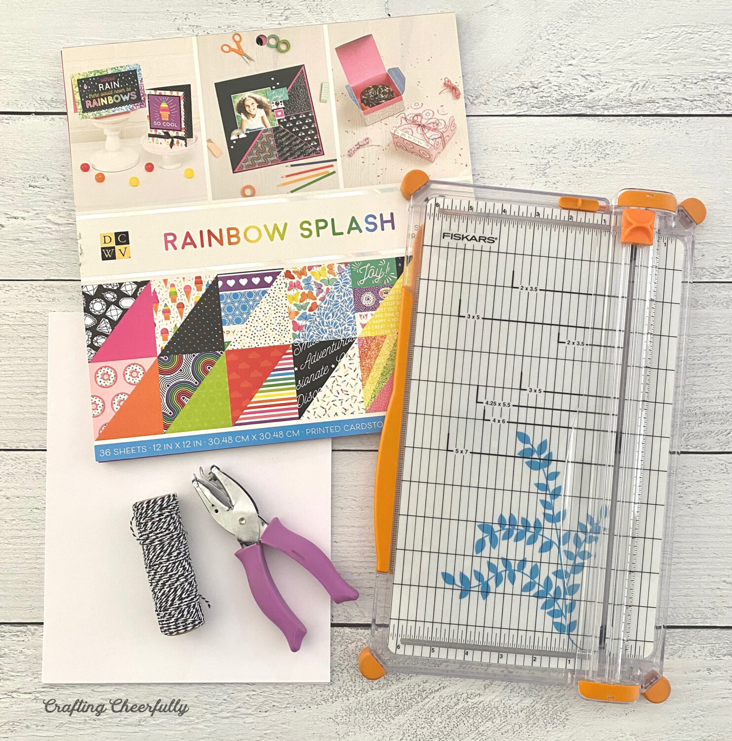 Supplies needed for making a summer journal including a paper trimmer, scrapbook paper, hole punch and bakers twine.