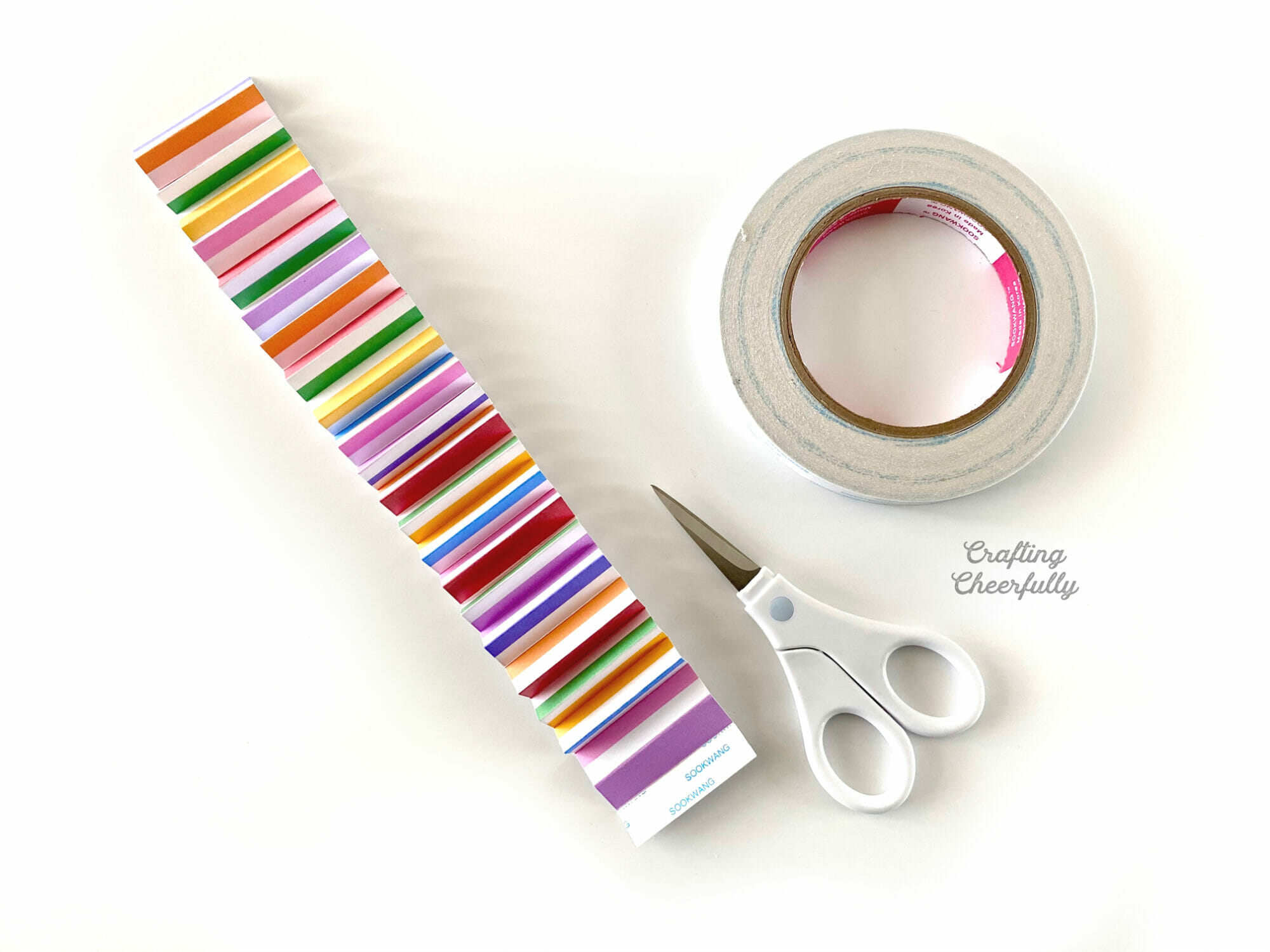 Strip of colorfully striped paper accordion folded with a smalls scissors and a roll of double-sided tape laying next to it.
