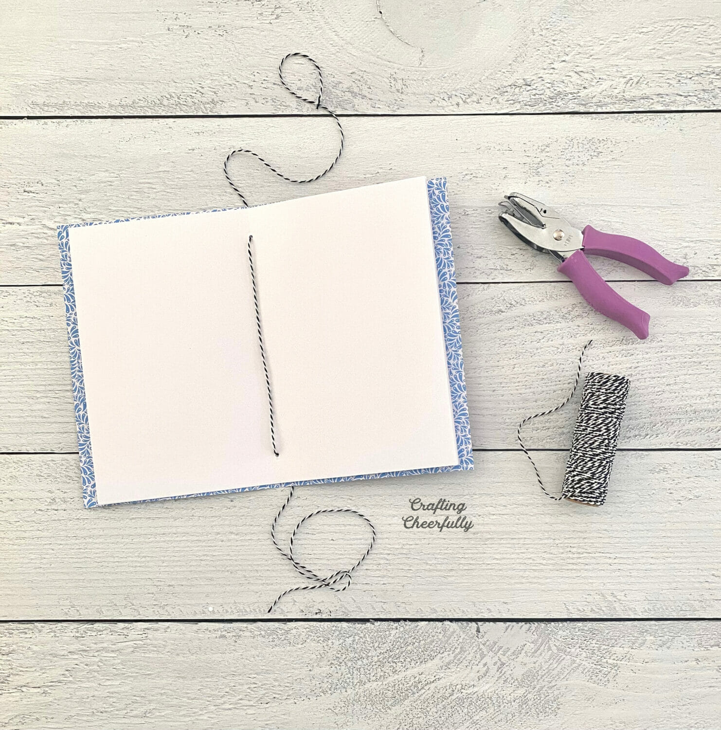 Paper journal with hole punch and roll of black and white Baker's Twine.