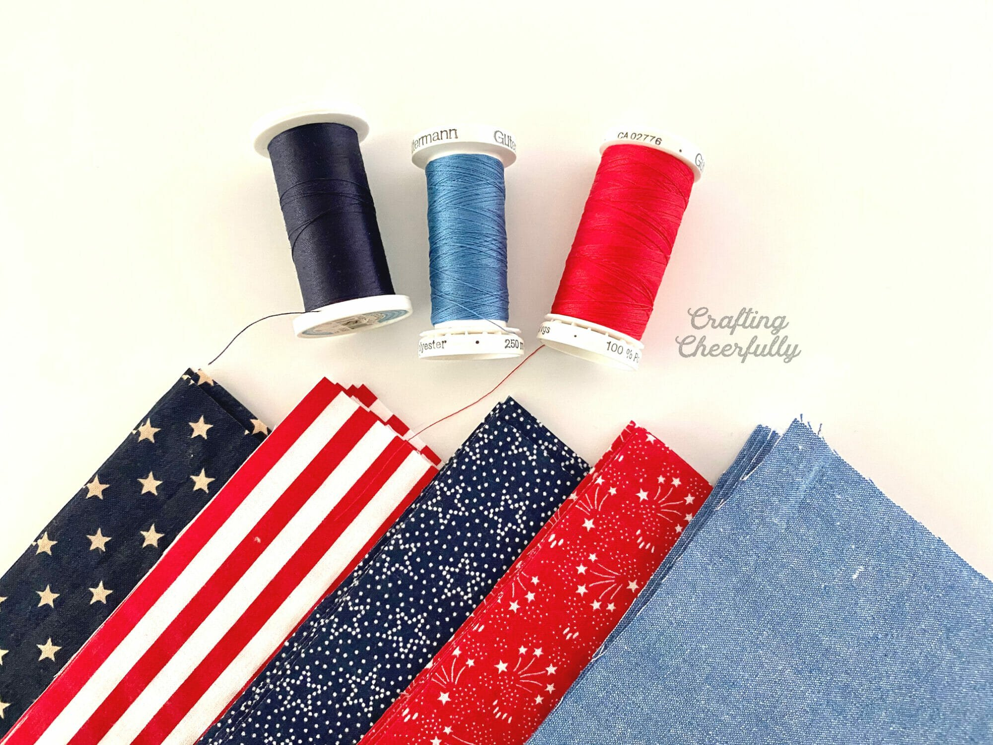 Red, white and blue fabric laying next to spools of coordinating thread.
