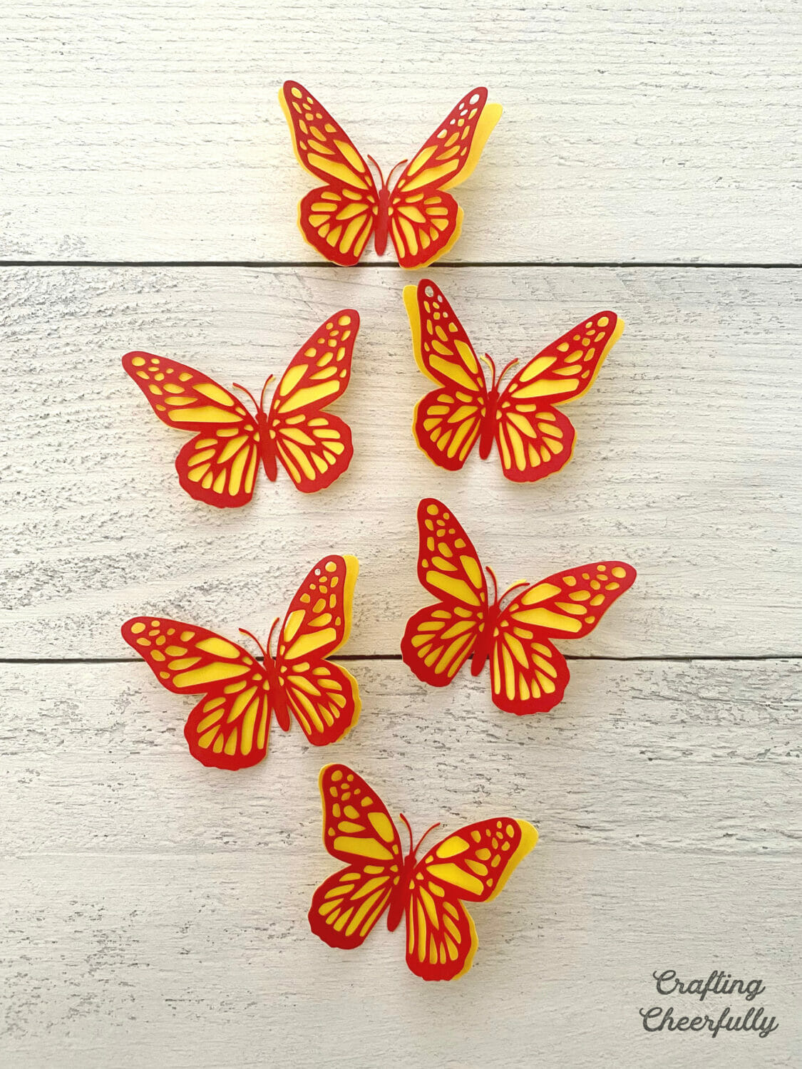 Red and yellow butterflies made from craft plastic are arranged on a wooden surface.