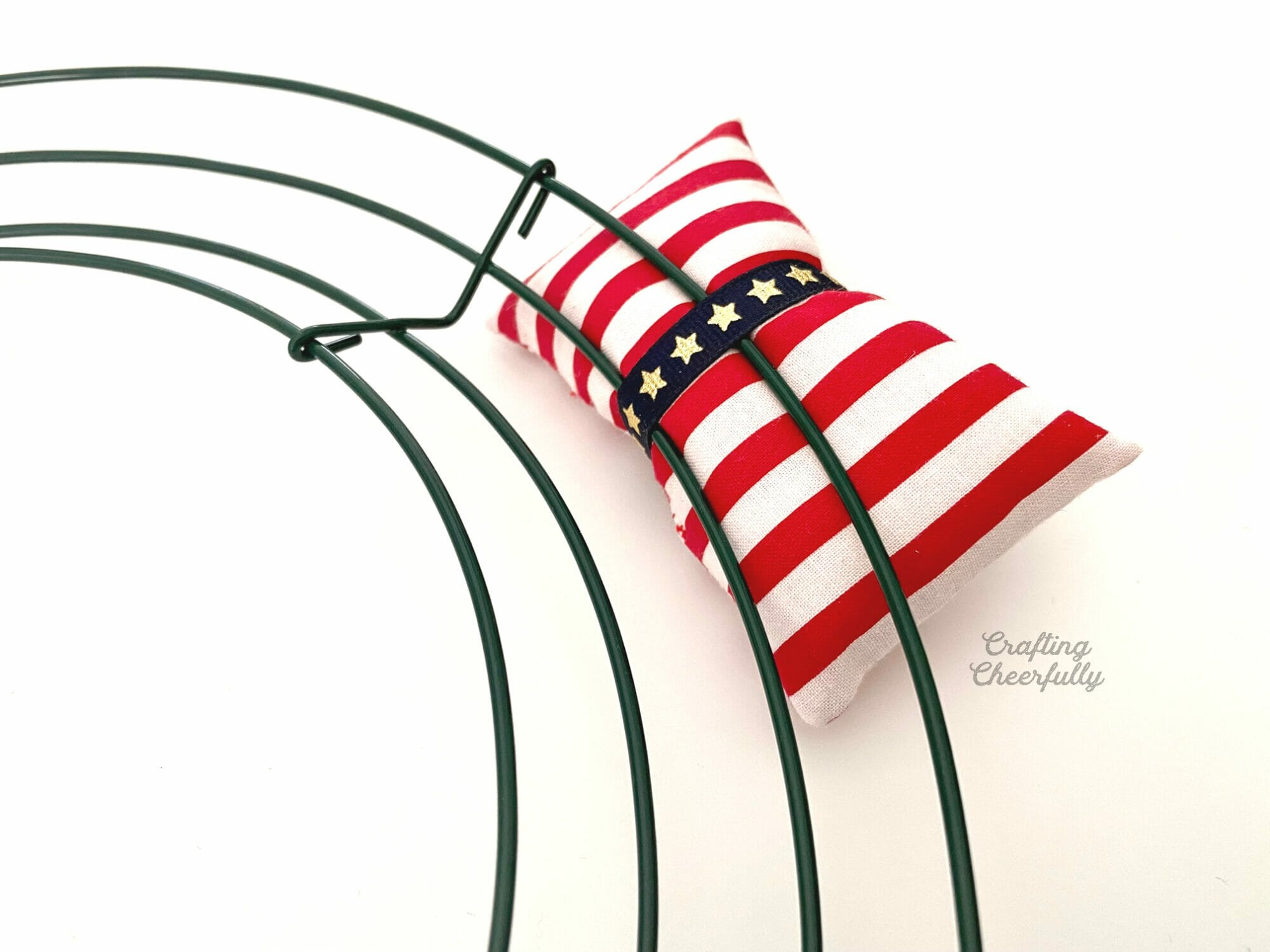 Red striped pillow tied to the metal wreath frame with blue star ribbon.