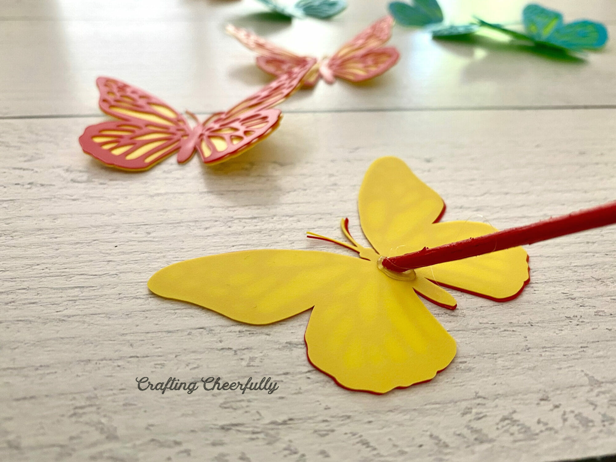 A red wooden dowel is glued to the back of a red and yellow butterfly.
