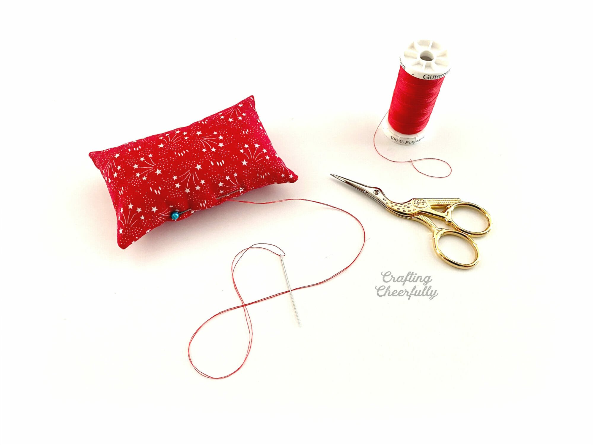 Red pillow with a pink in it laying next to a red spool of thread and stork scissors.