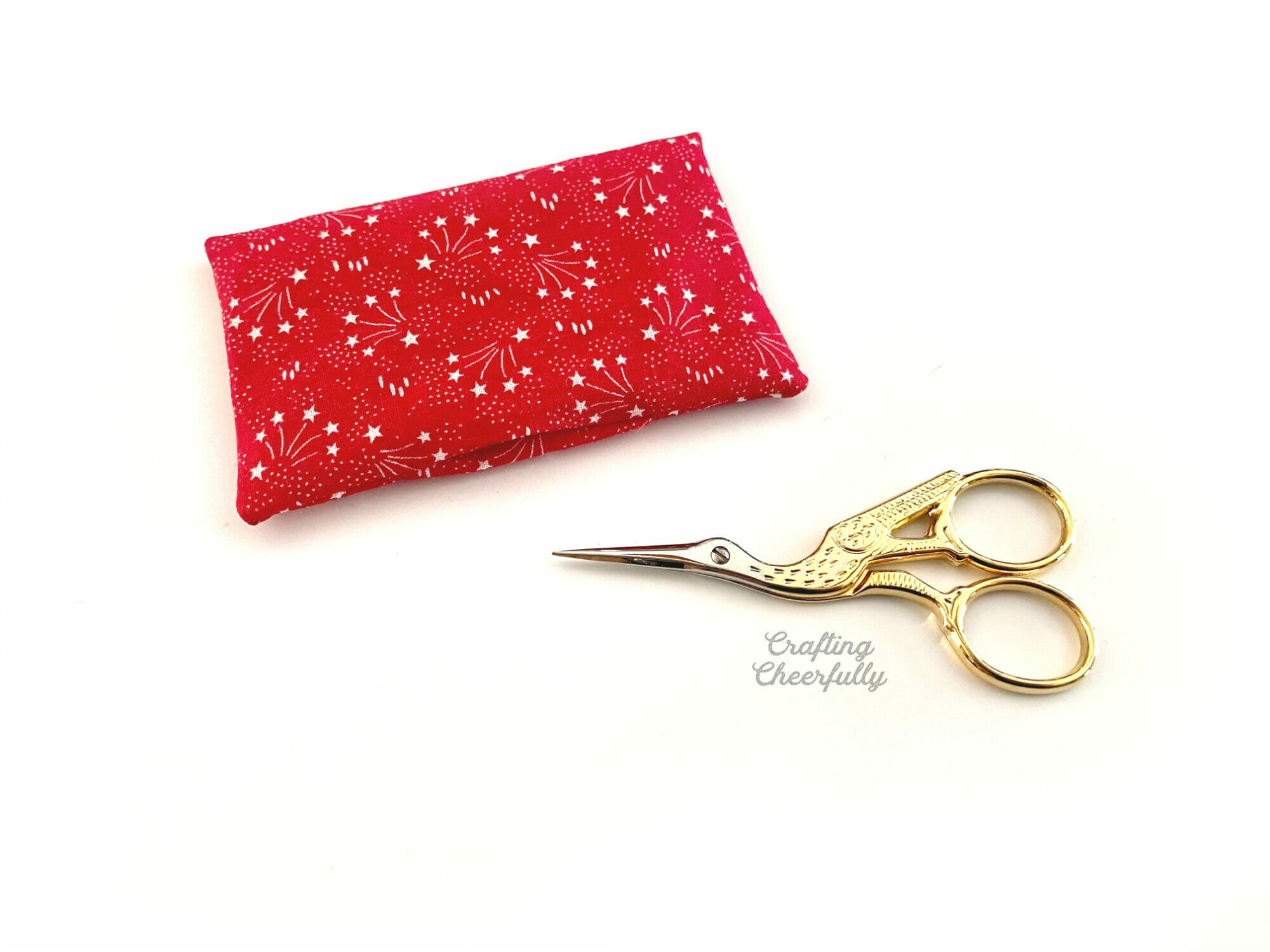 Red pillow is turned right side out with a visible opening. Laying next to a gold stork scissors.