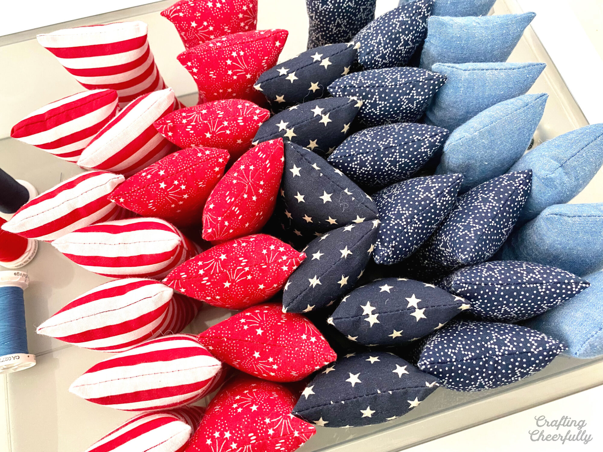 A tray of red, white and blue pillows stuffed and ready to use.