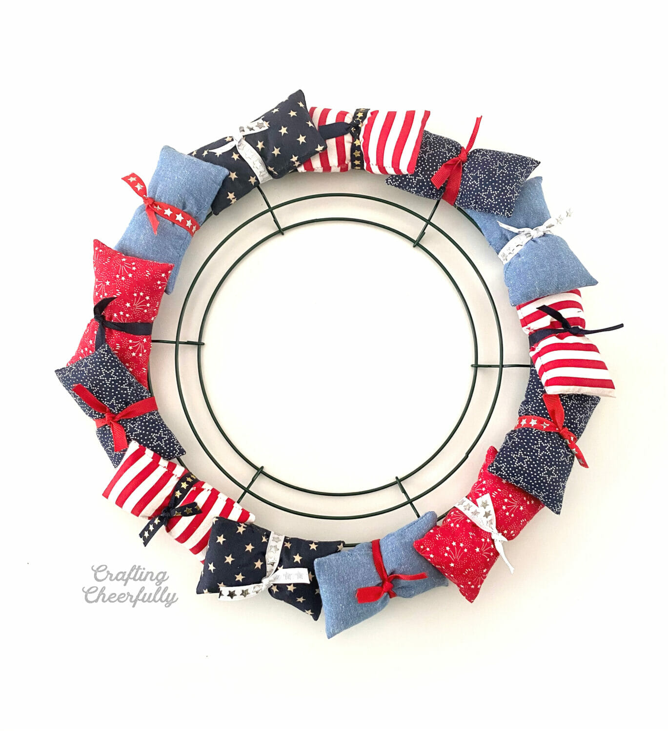Fabric pillows tied around a wire wreath frame using ribbon.