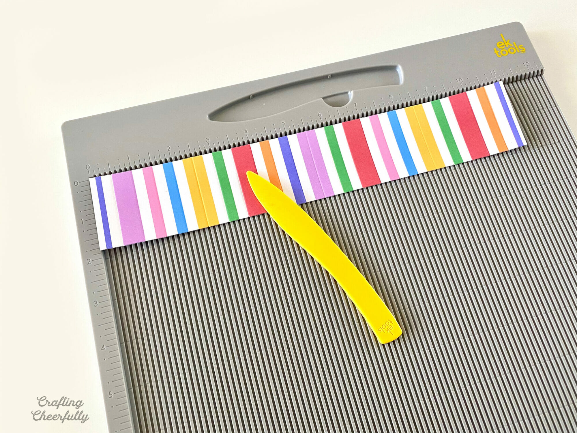 Piece of colorfully striped paper on a scoring board with a yellow stylus.