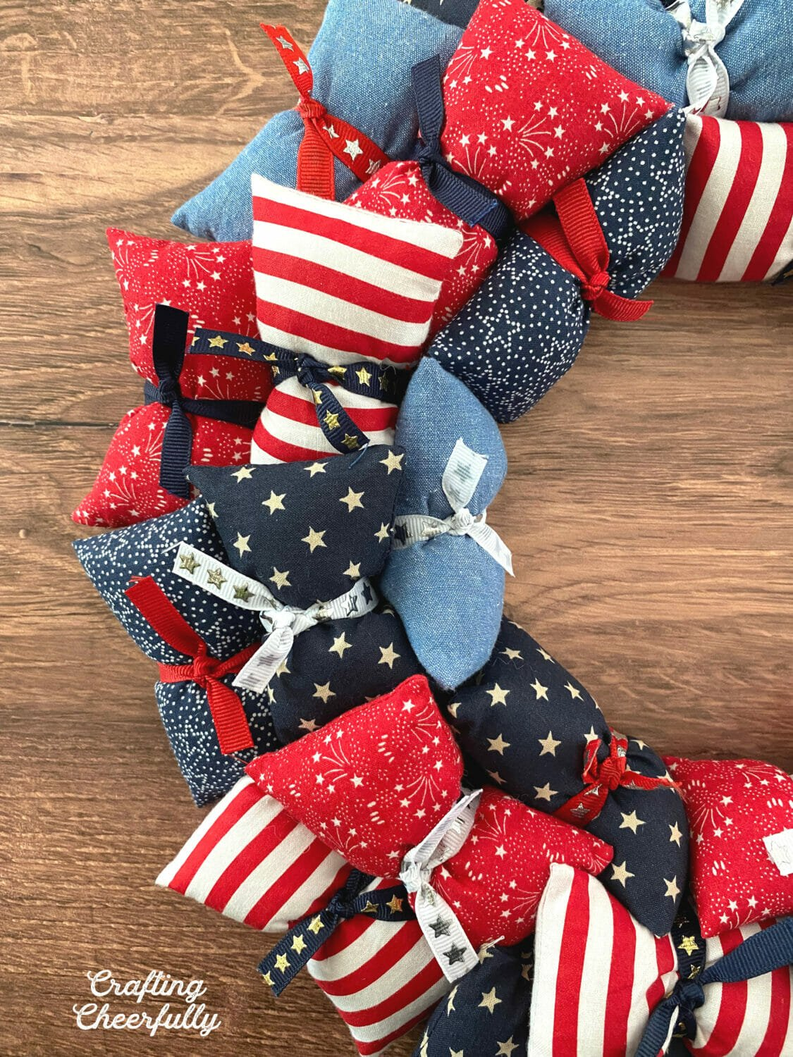 Red, white and blue pillows tied to a metal wreath frame wth ribbon.