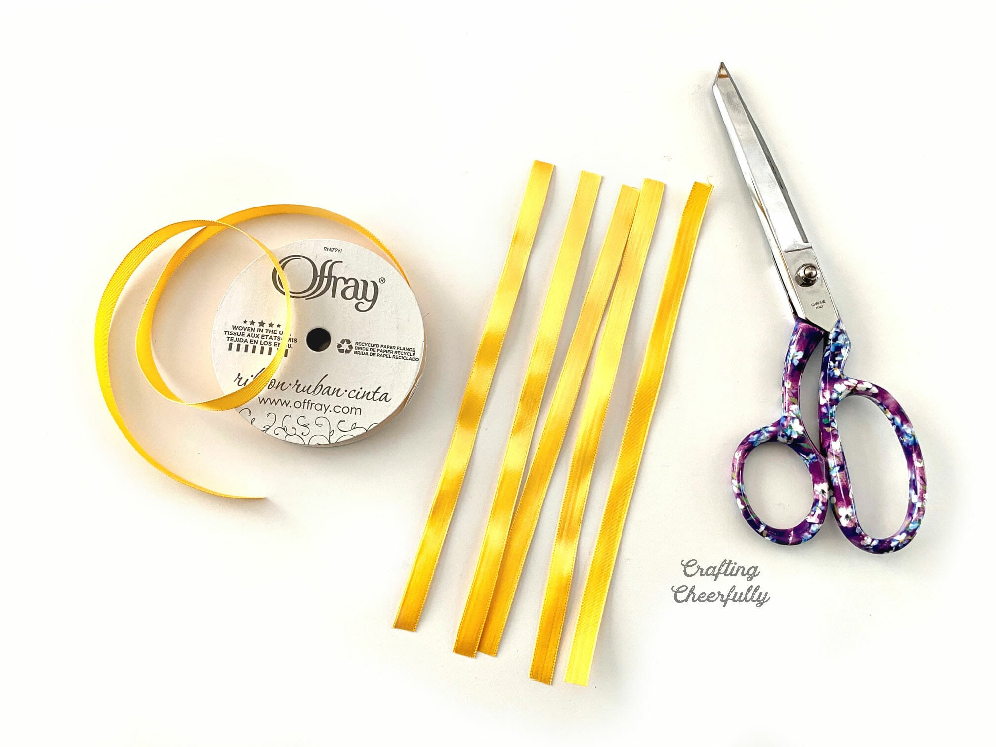 Strips of yellow ribbon lay next to a scissors on a white table.