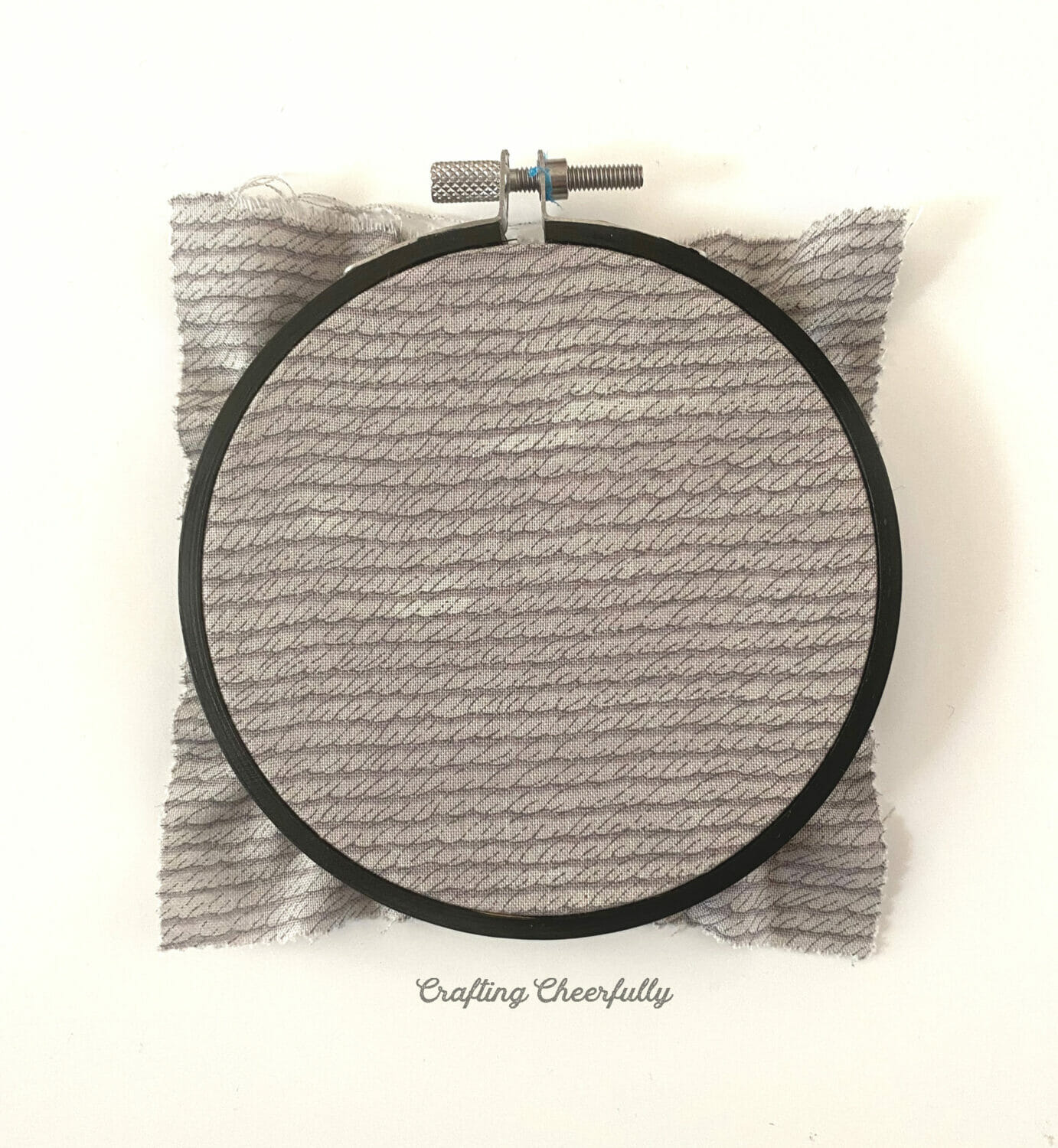 Gray fabric in a black embroidery hoop.