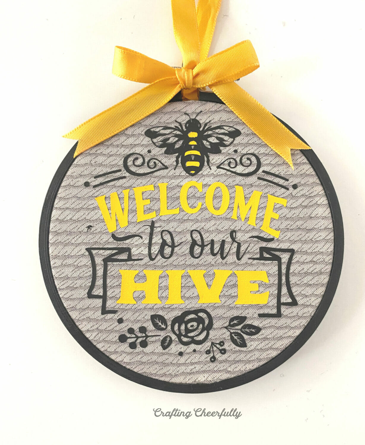 """Embroidery hoop with the words """"Welcome to our Hive"""" applied to an embroidery hoop with a yellow bow."""