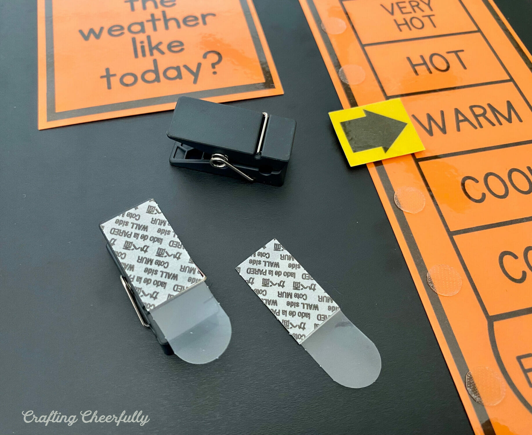 Black clips used to hold calendar printables on the chalkboard.