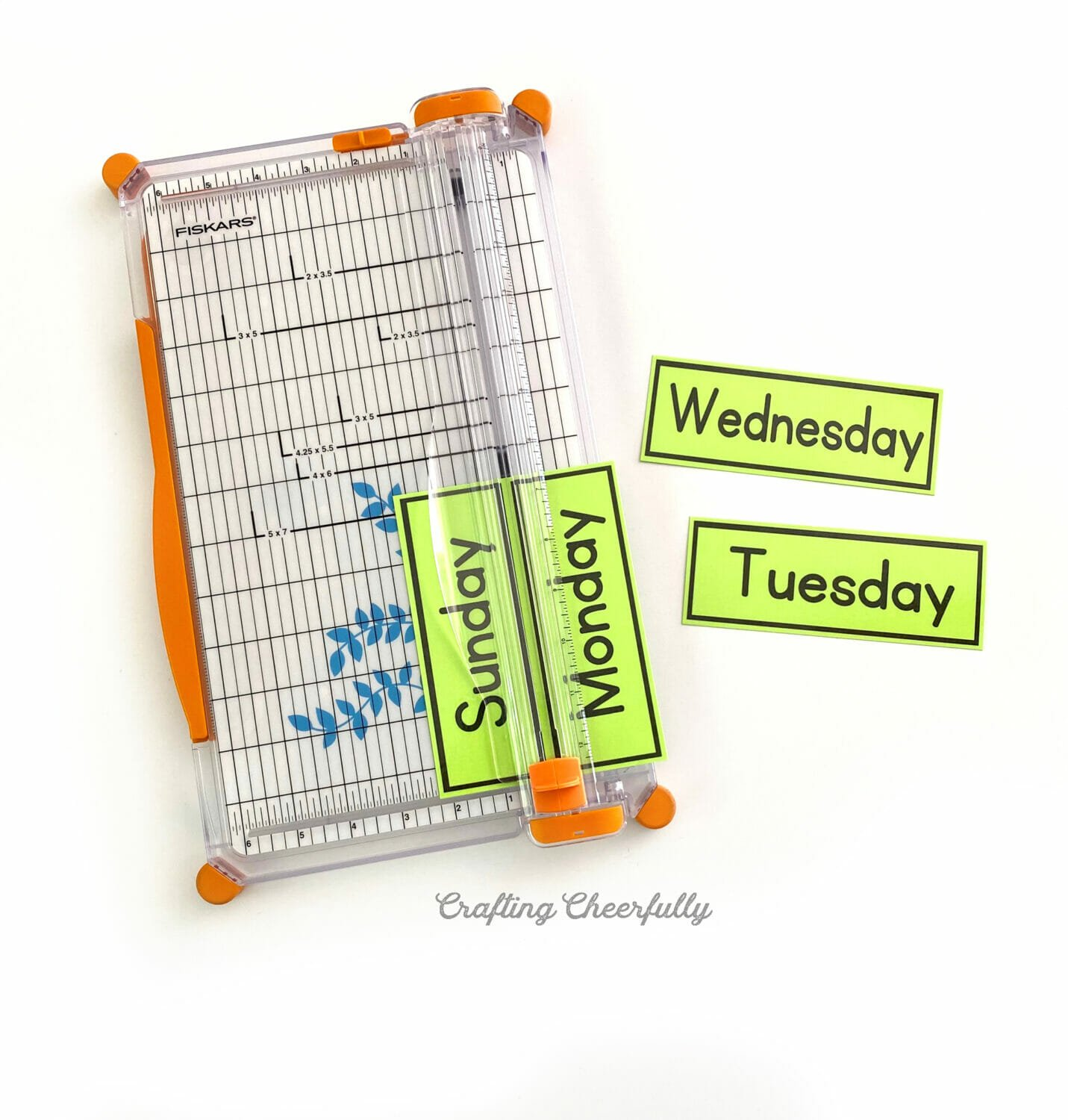Green paper calendar printables being trimmed in a paper trimmer.