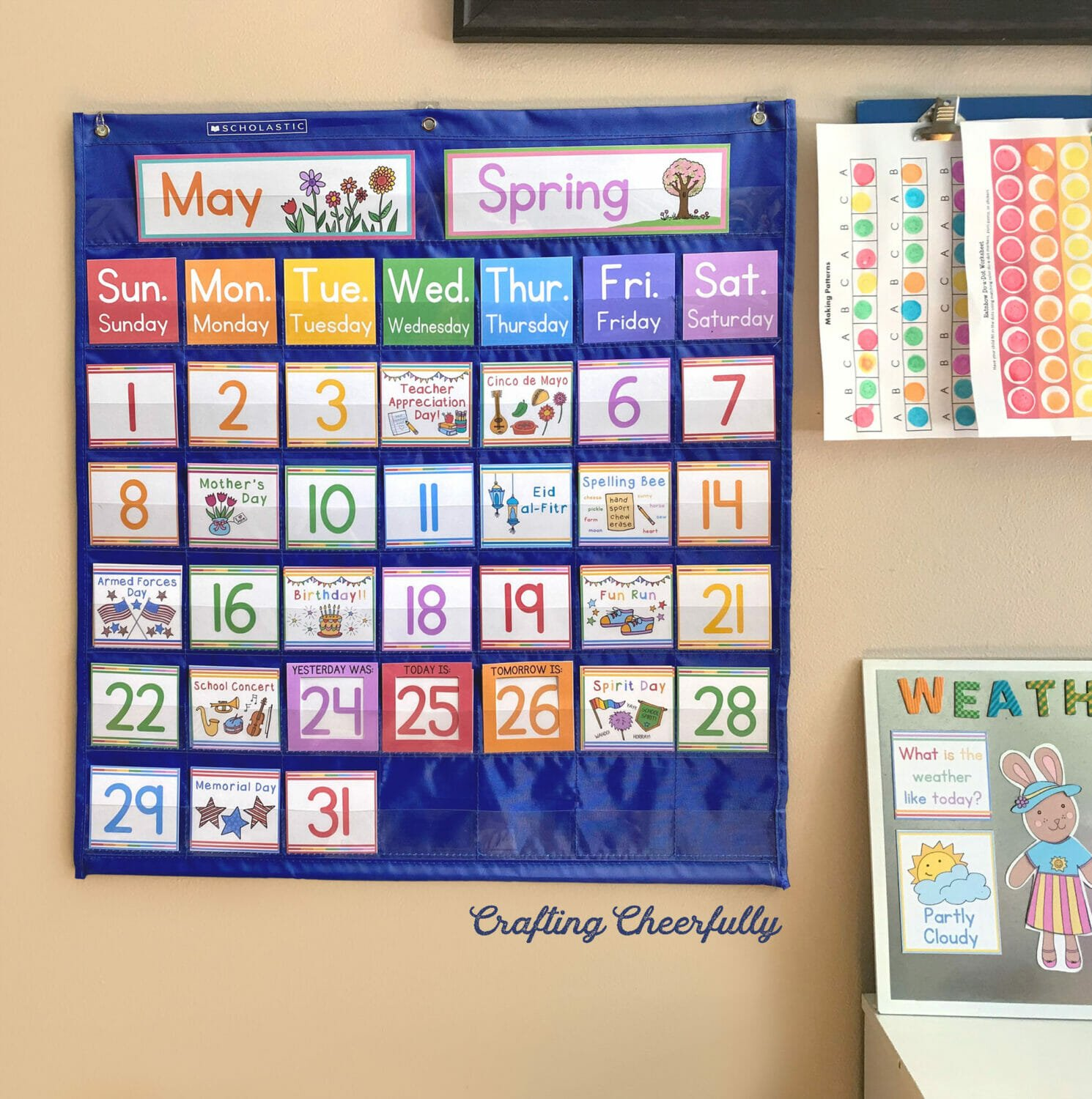 Pocket chart calendar hanging on a wall with colorful kids drawings by it.