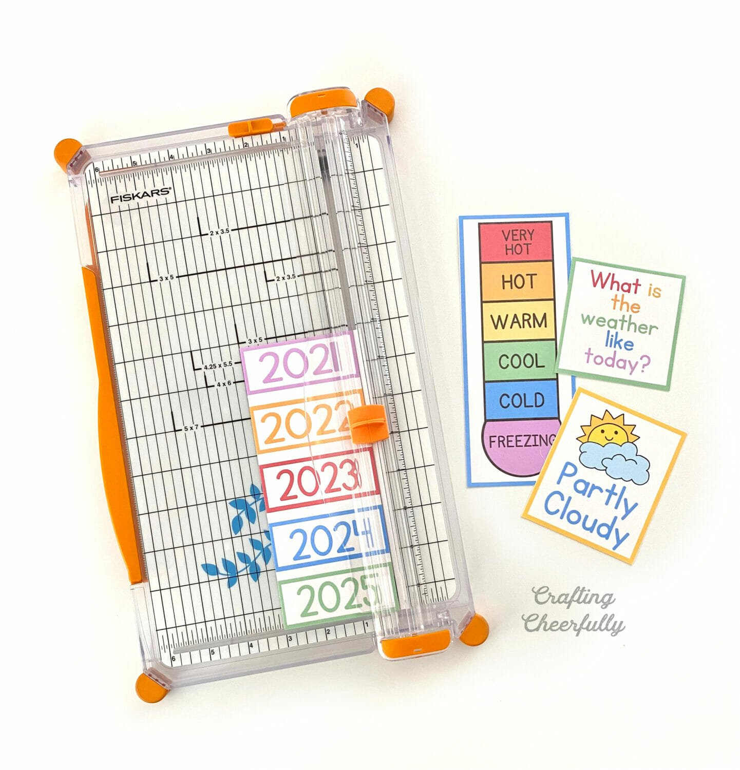Calendar printables being cut by a paper trimmer.