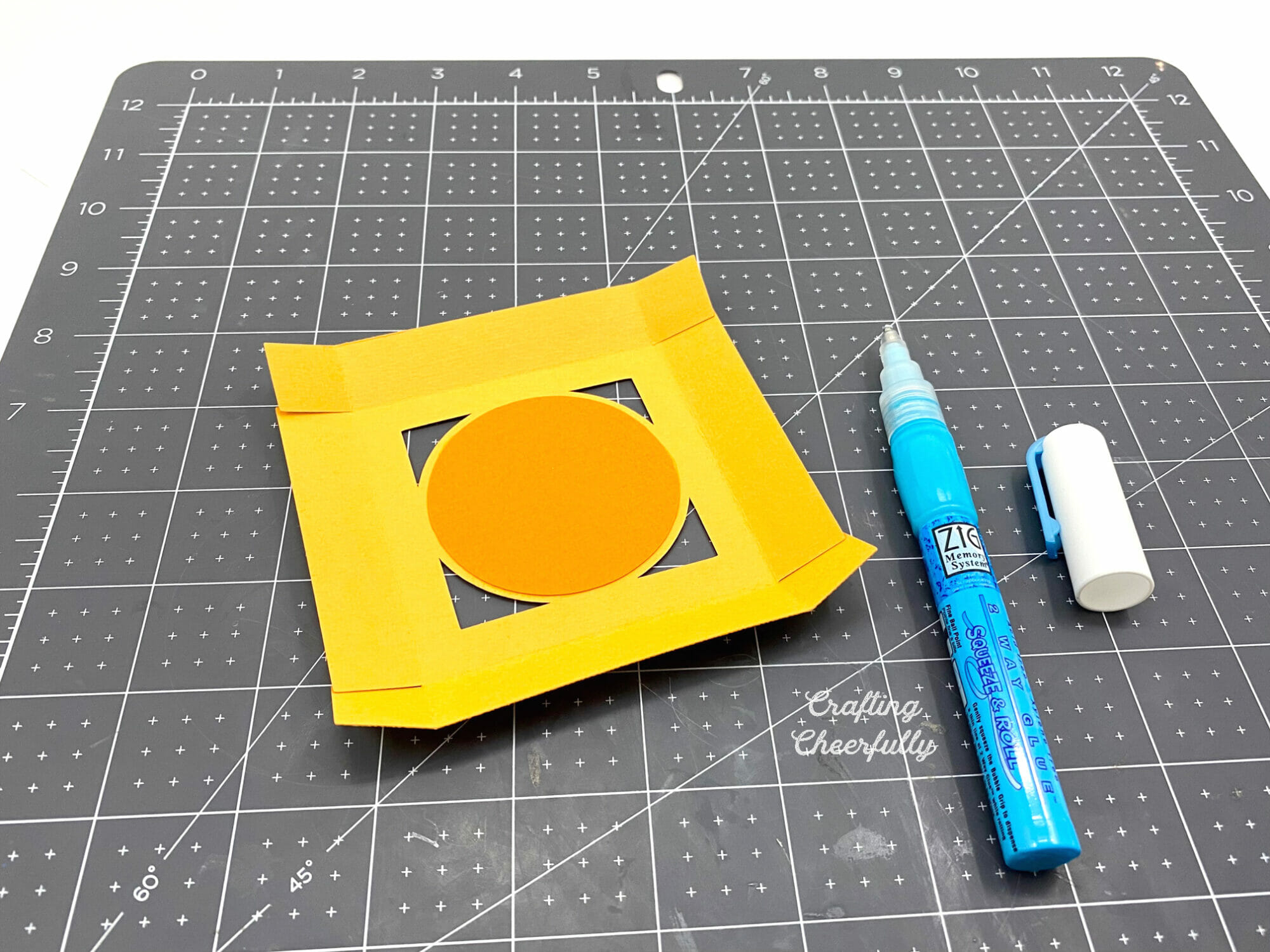Fruit favor box lid being assembled on a black cutting mat with glue