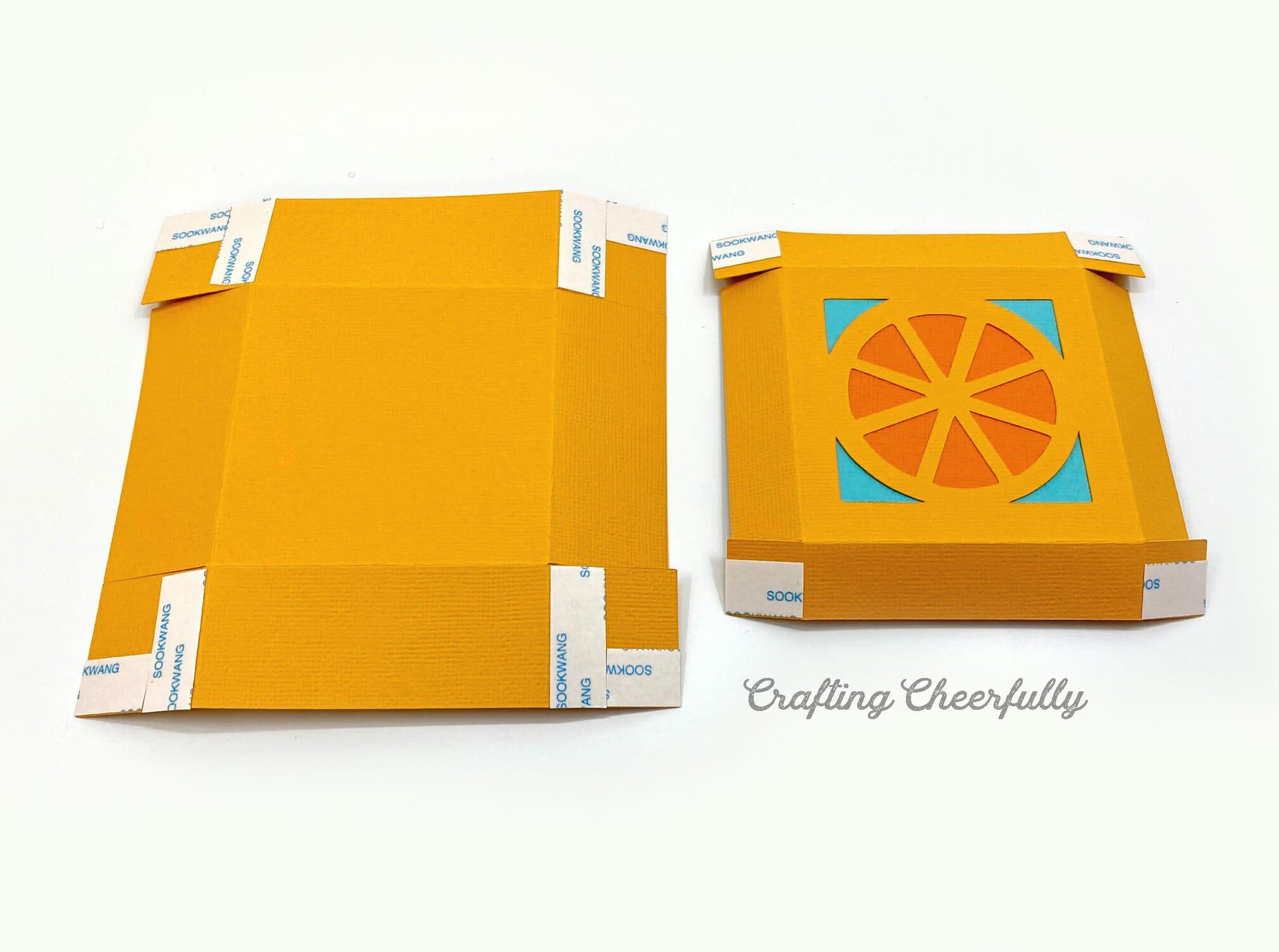 Orange fruit box with tape on the corner edges.