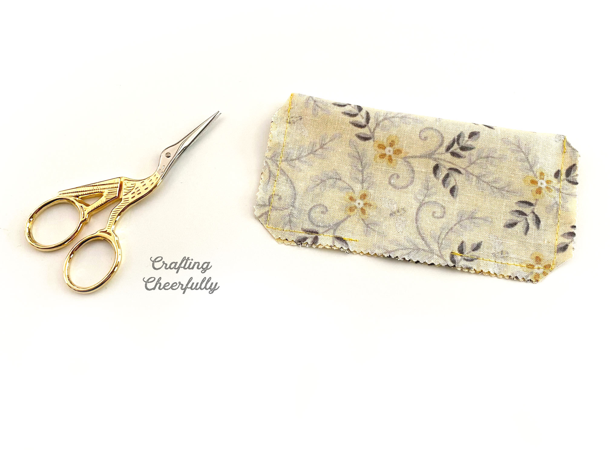 Mini pillow lays next to a mini gold scissors.