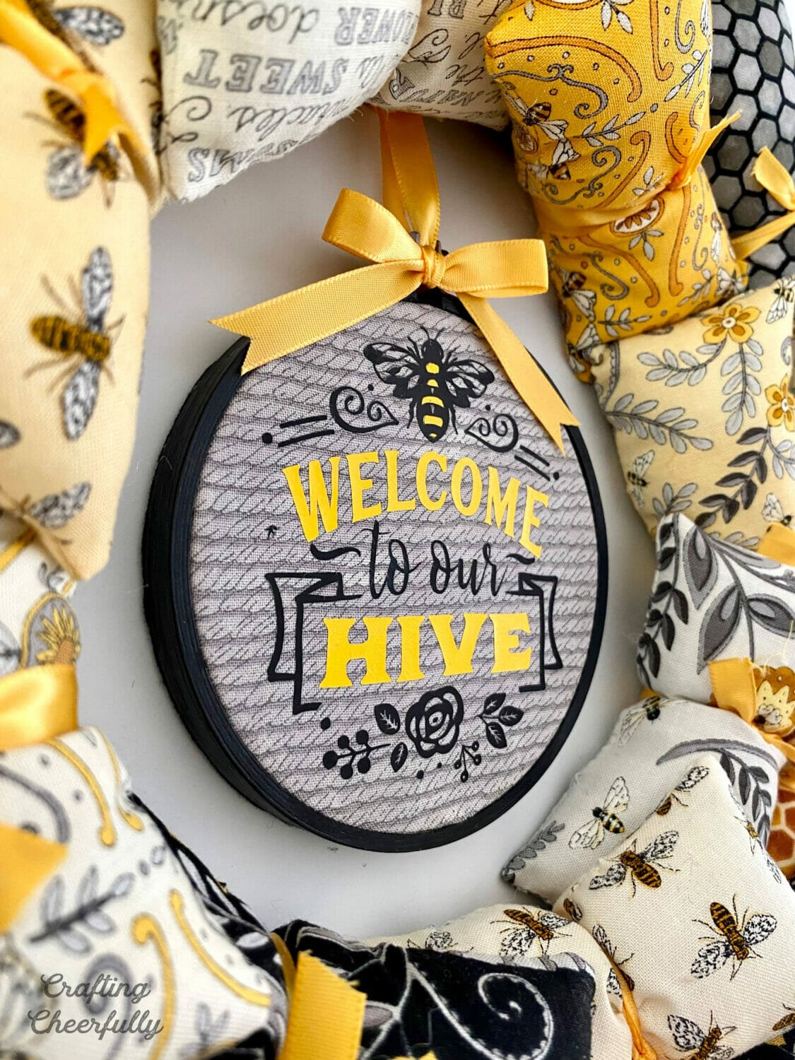 Welcome to our Hive bee wreath close up of embroidery hoop hanging in the center.