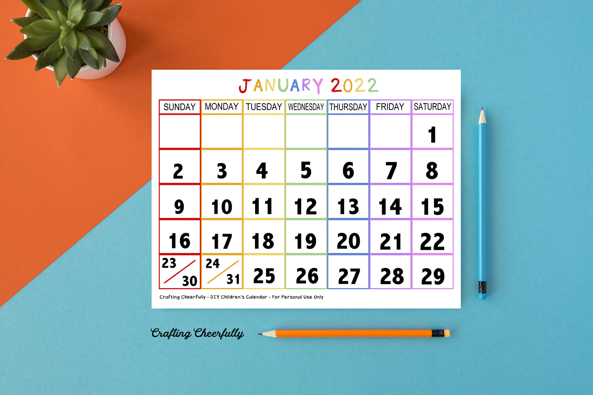 2022 Calendar page laying on an orange and teal background with pencils and a mini plant.