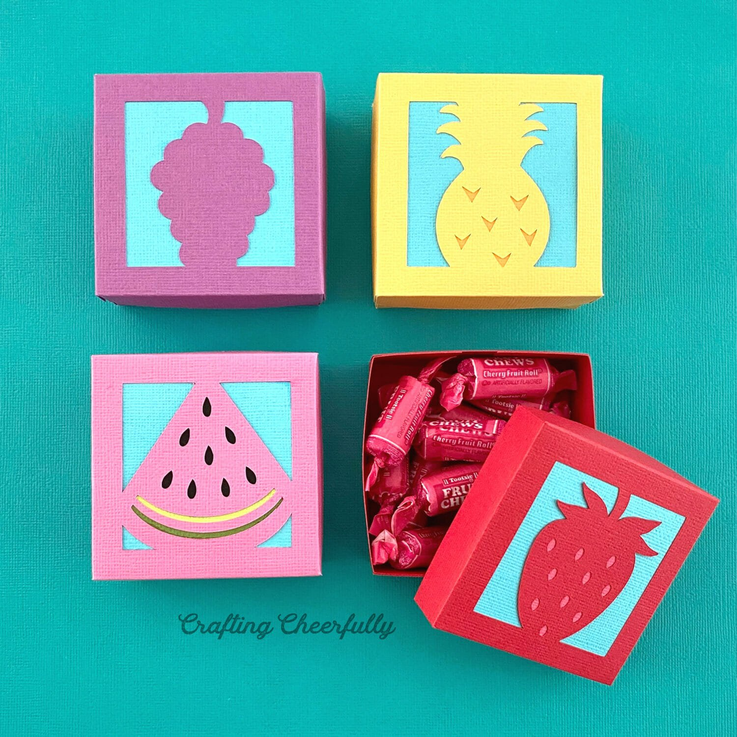 Four colorful boxes with fruit on them sit on a bright turquoise background.
