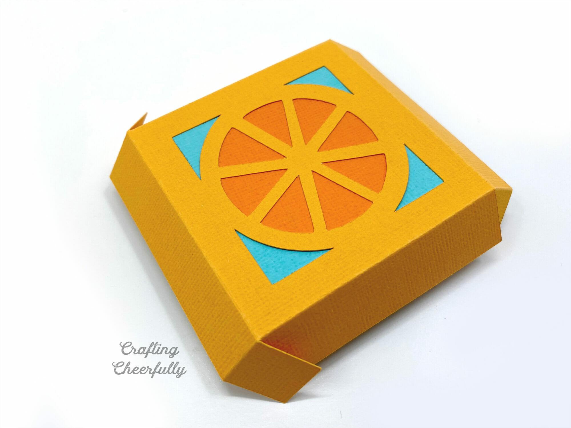 The lid for a Orange tutti frutti party favor box.