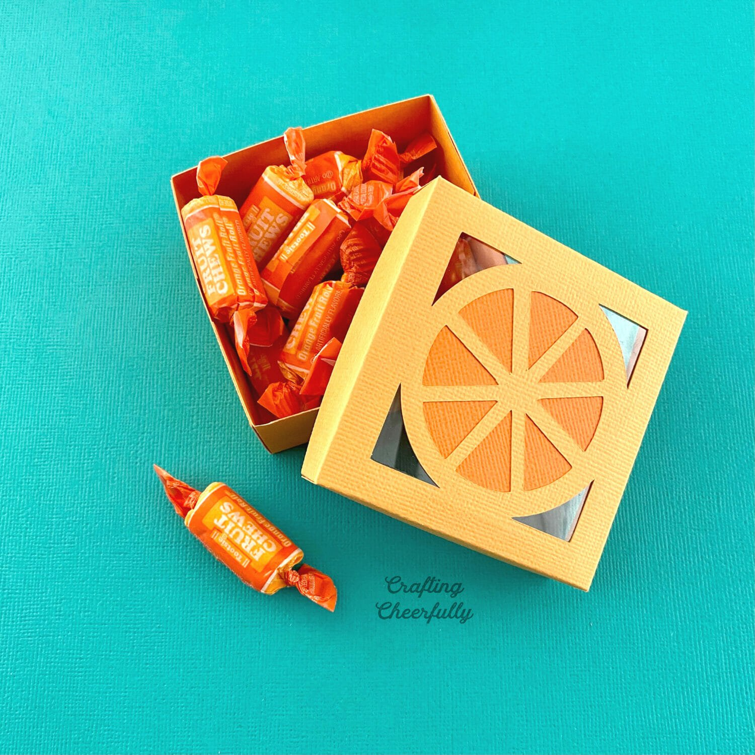 Orange tutti frutti box filled with orange candy on a turquoise background.