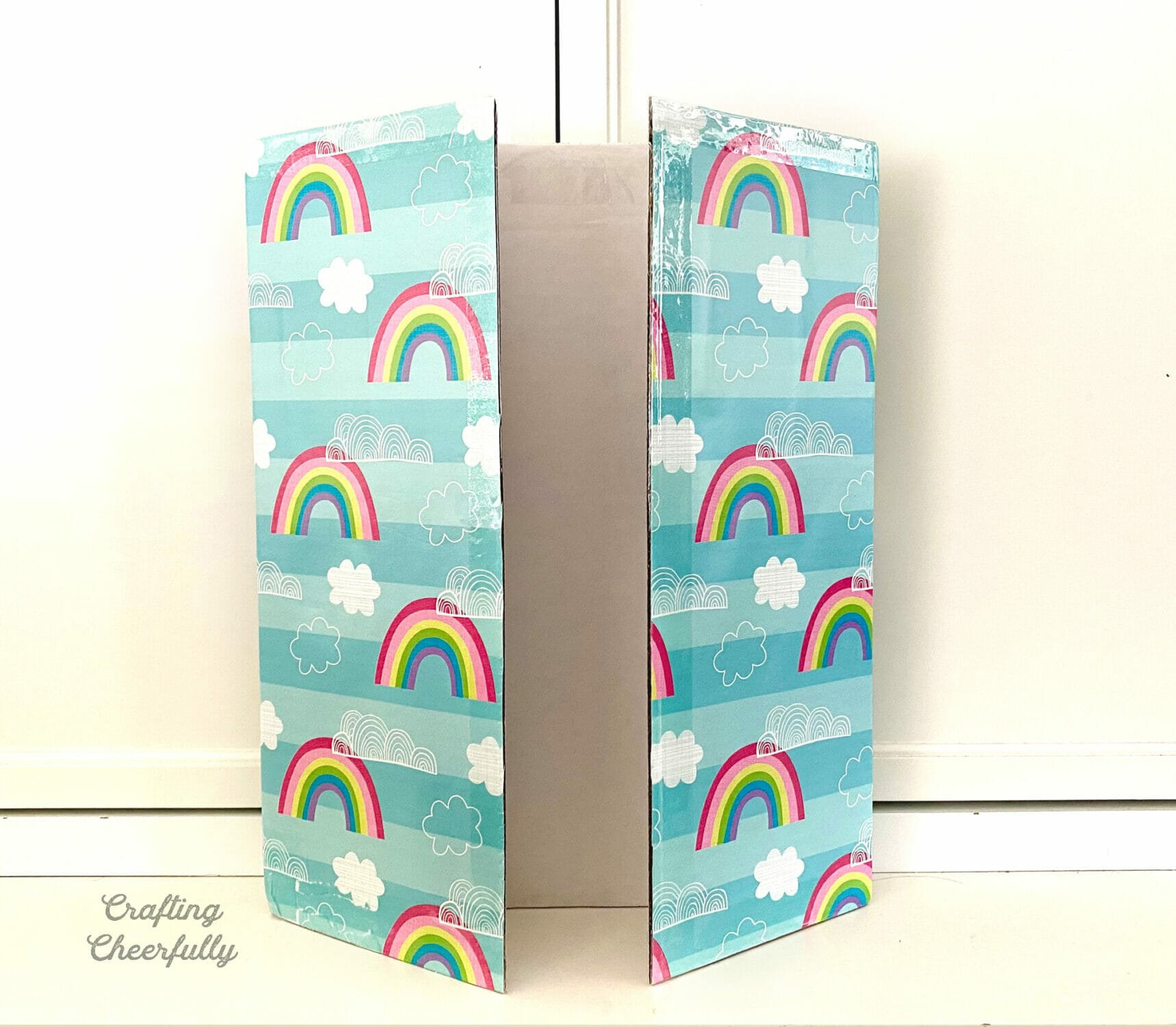 Tri fold board covered in rainbow and cloud wrapping paper.