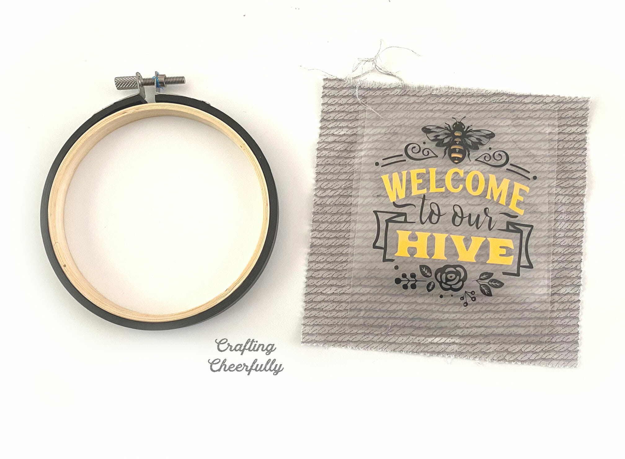 Black embroidery hoop lays next to a piece of gray fabric with black and yellow iron-on applied.