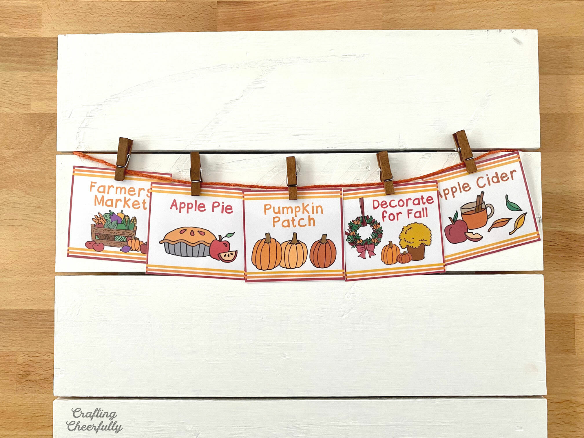 Fall activity cards are pinned to a line of orange twine.