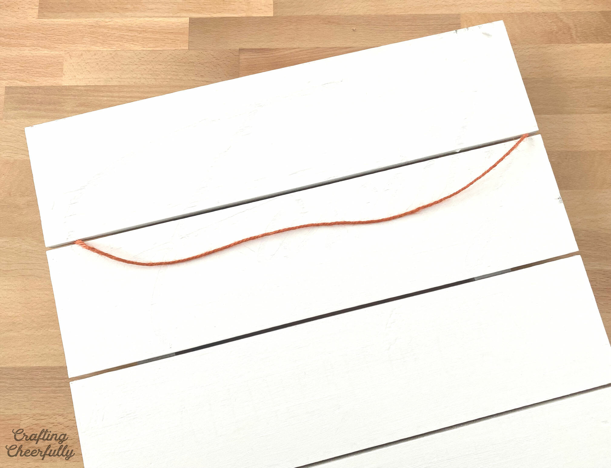 White board with orange twine taped to it.